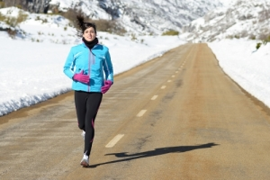 woman running in snow lined road to combat SAD